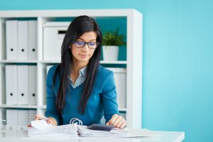 Young businesswoman with glasses calculates tax at desk in office